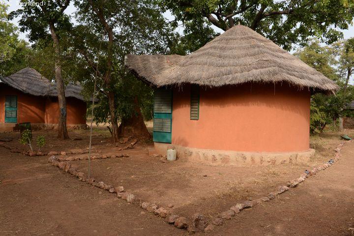 cases sous les arbres crépi en orange avec les portes et fenêtres peintes en vert  avec bordures en pierre,