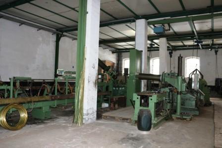 Hier werden die gelieferten Messingrollen in gerade Rohre gezogen, bevor sie zur Weiterverarbeitung in die Haupthalle kommen