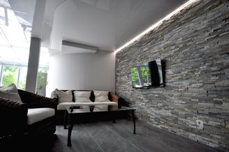 Wohnraum mit Steinwand, Lichtkanal-Technik und weißer Lackspanndecke (deckenpartner GmbH).