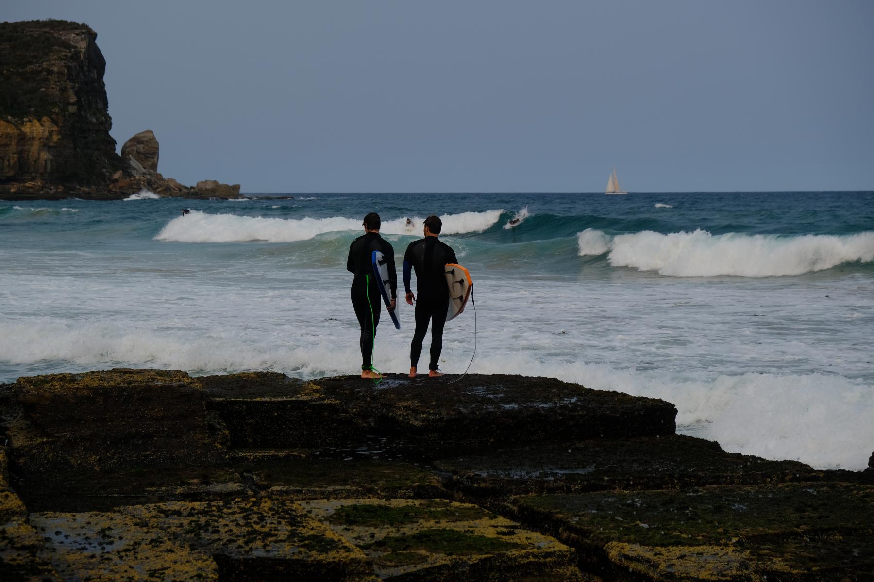 Zwei noch etwas unerfahrene Surfer suchen eine Stelle, um zu den Wellen zu gelangen
