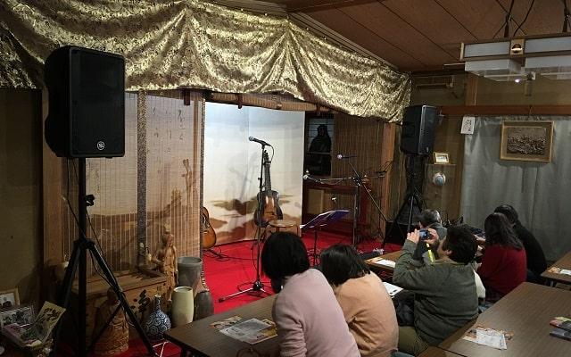 新小岩にある應無寺(おうむじ)の音楽ステージにフォークギターがセットしてある場面