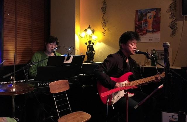 ギタリスト「マサさん」と奥さん「ヒロコさん」夫婦音楽ユニット「RoseHeart」が下北沢「Blue Moon」でライブをやっている場面