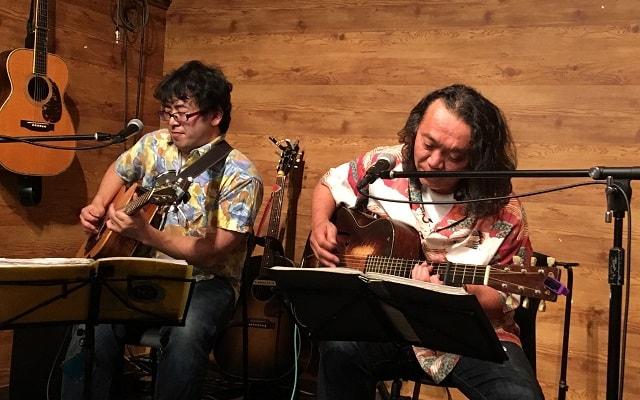 アコギのギタリスト2人がギターソロの掛け合いをしている場面