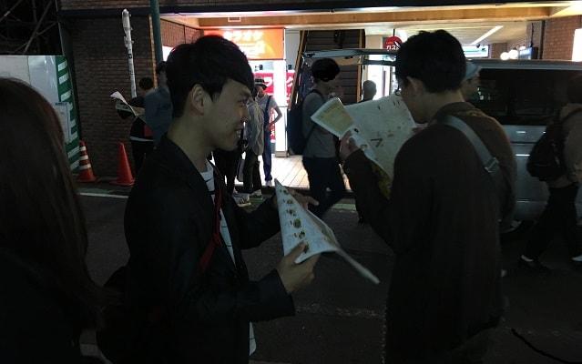 下北沢駅の南口でカレーフェスのマップを眺める2人の男性