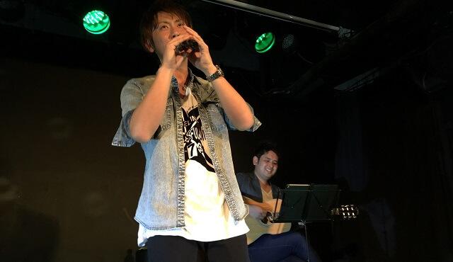 コモロカズキが六本木ライブハウス「虎寅虎」のワンマンライブで歌っている場面