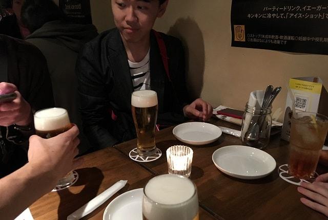 下北沢のバー「SHARE(シェア)」のテーブル席にビールが運ばれてくる場面