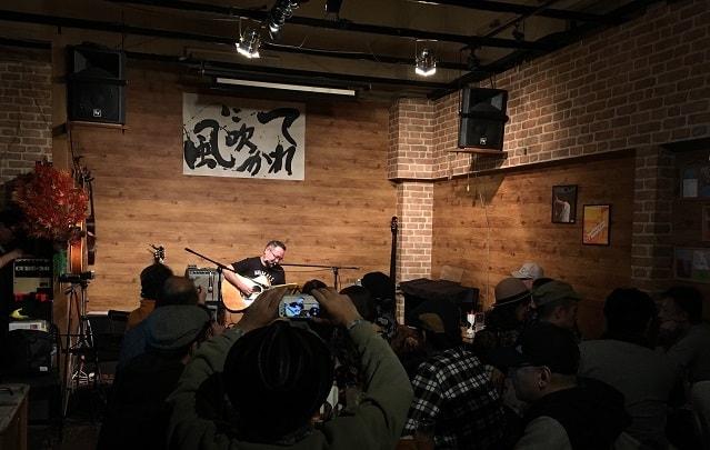 東京都大森のライブバー「風に吹かれて」でライブが行われている場面