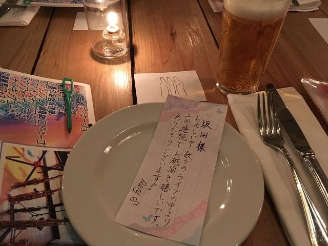 渋谷ナヴァーにて開催されたディナーショーのテーブル席に並んだ食器とメッセージカード