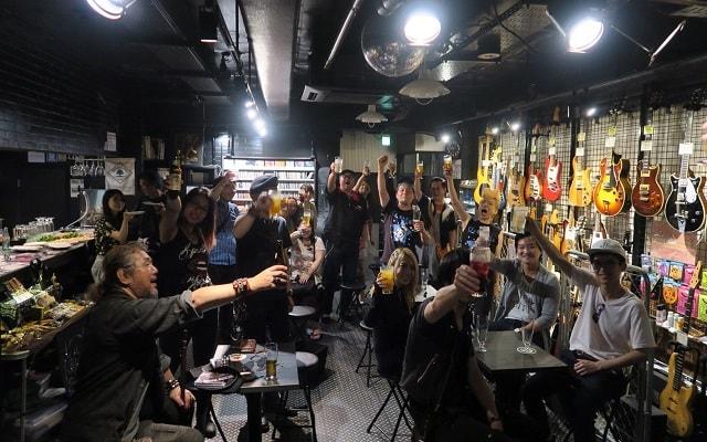 上野ファビュラスギターズにて行われた打上げでの乾杯の場面