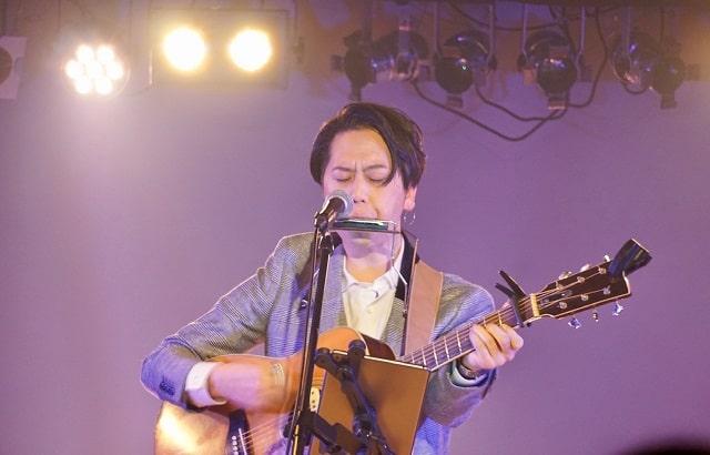 シンガーソングライターのカズが渋谷スターラウンジでワンマンライブの演奏をしている場面