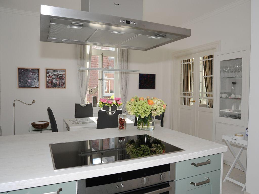 Offener Küchenblock mit Blick auf Essbereich und Doppelflügeltür zum Wohnzimmer