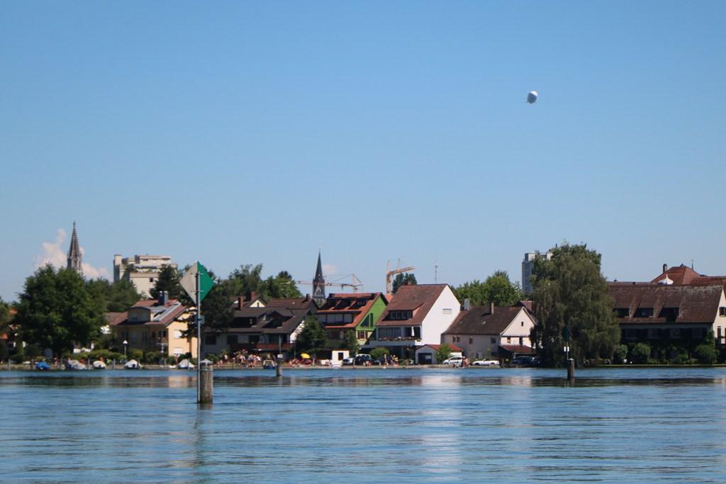 Rheinabwärts in Richtung Seerhein, die historische Altstadt von Konstanz im Hintergrund oben rechts ein Zeppelin