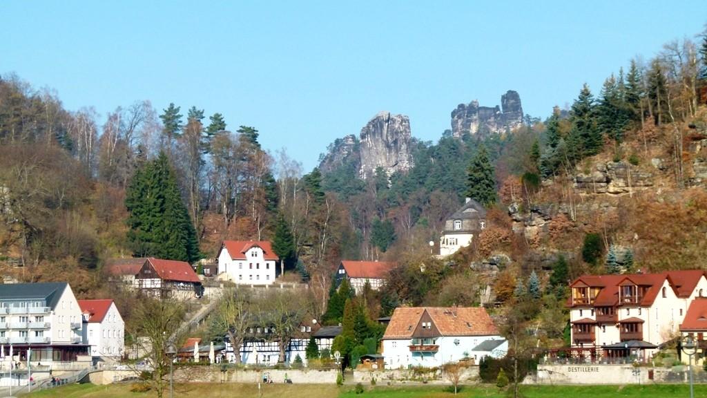 Teilansicht des Kurortes Rathen mit den Kletterfelsen Talwächter und Lokomotive im Hintergrund.