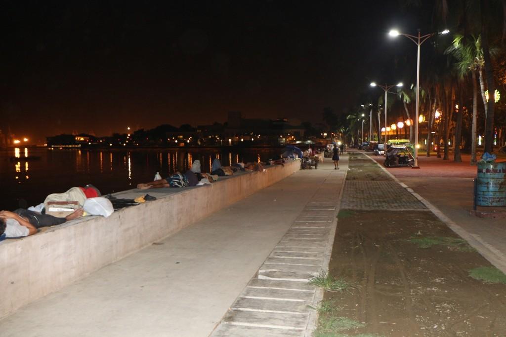 """Auf der schier endlosen Mauer der Manila Bay """"nächtigen"""" Massen von Menschen, ein für uns fremdartiges Szenario"""