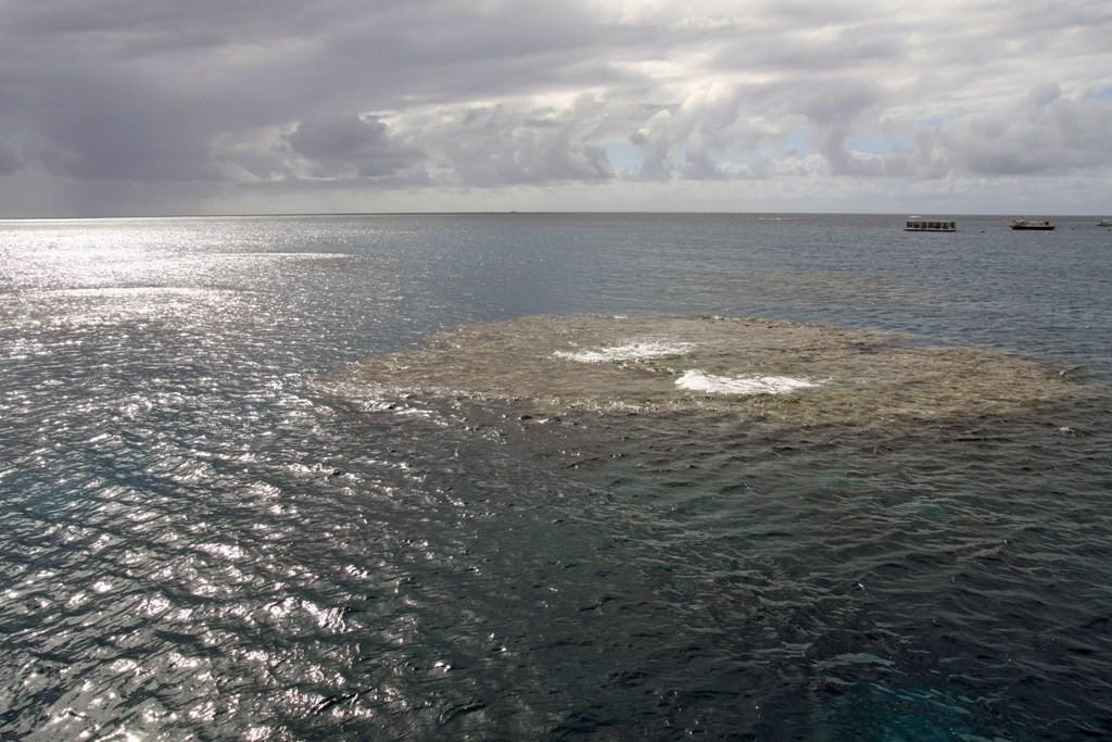In Vordergrund eine Korallenbank, nur spärlich vom Meerwasser umspült!