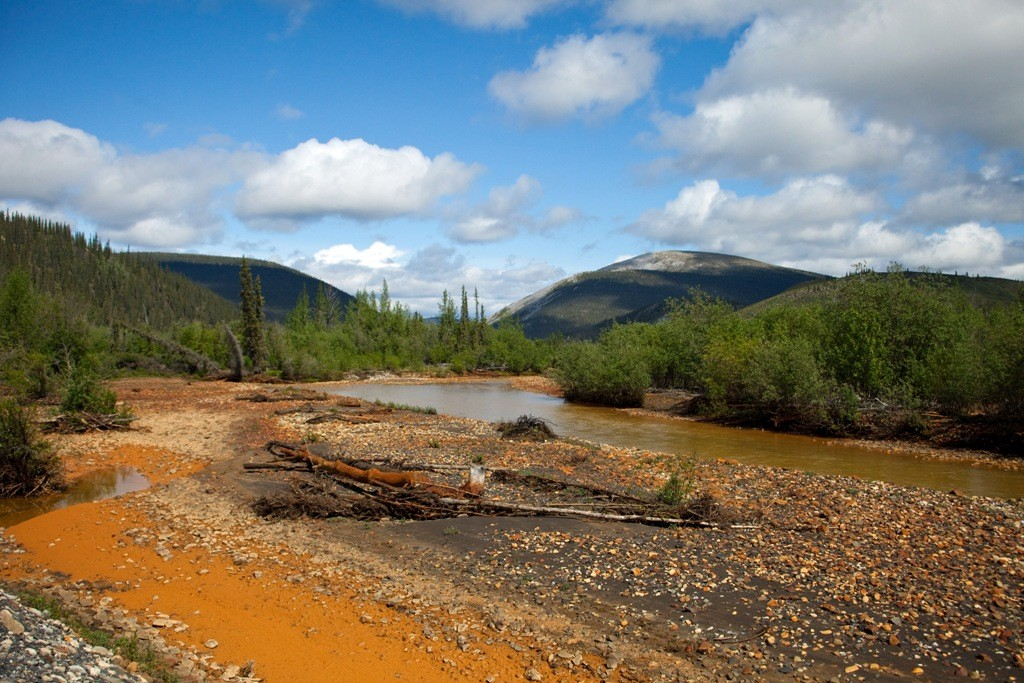 Blick auf den Red Creek, eindeutig erkennbar, die mineralischen Ablagerungen im und am Flussbett.