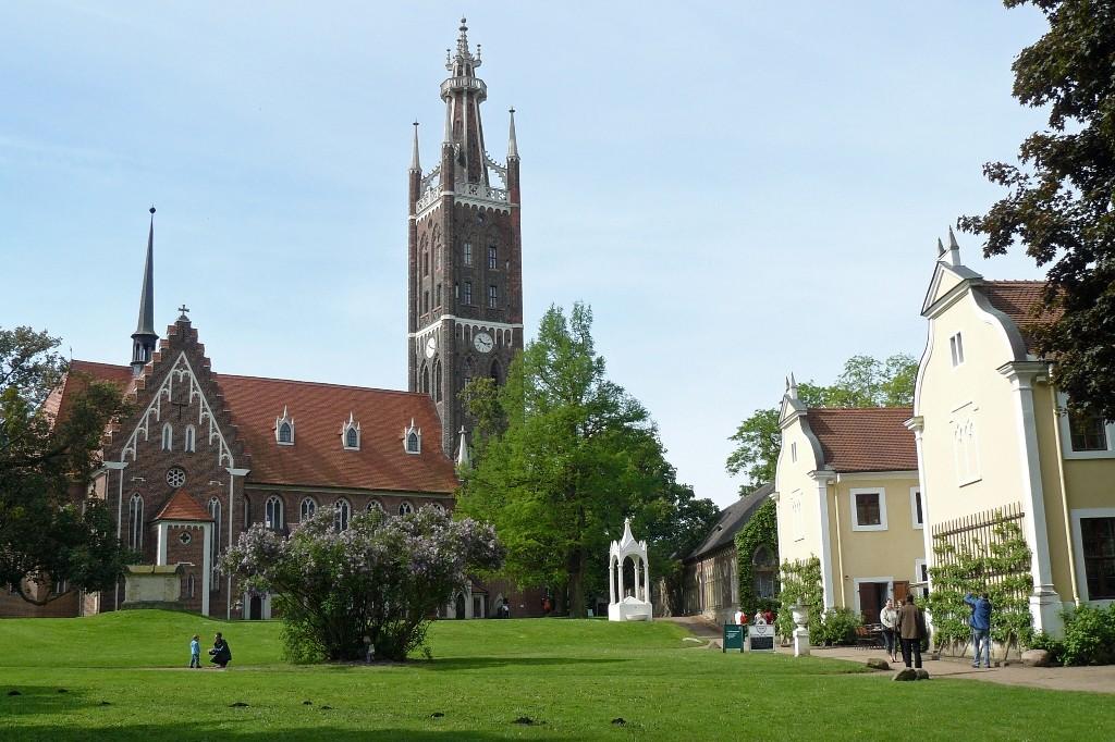 Die St.-Petri-Kirche von Wörlitz mit dem 66 m hohen Bibelturm und dem Kirchhof mit Sarkophag