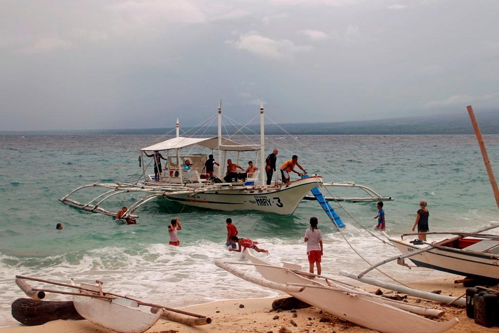 Unser Tauchboot vor Anker und es tummeln sich die Kinder im Brandungswasser!