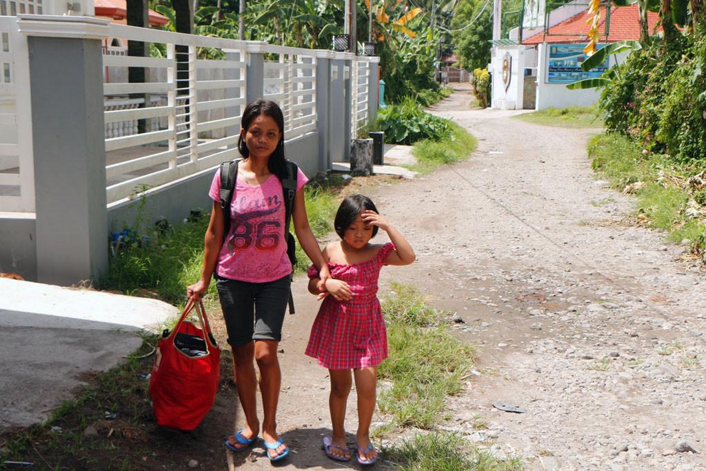Mylin nebst Patti auf dem Weg zum Busstop an der National Road in Dauin. Hinten rechts die Toreinfahrt zum Garcey Dive Resort!