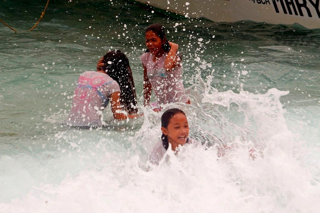 Filipinos und Filipinas in der Brandung vorm Bug unseres Tauchbootes!