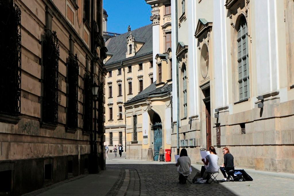 Kunststudenten bei herrlichen Wetter vor dem Universitätsplatz in Aktion