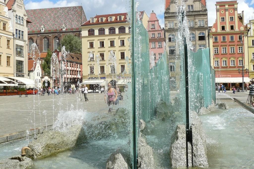 Der gläserne Springbrunnen auf der Westseite des Rynek passt eigentlich nicht in seine historische Kulisse. Seit 2001 steht er hier und spaltet die Breslauer Bevölkerung. Die einen wollen ihn weghaben, die andern lieben ihn (ich auch), weil er im Sommer f