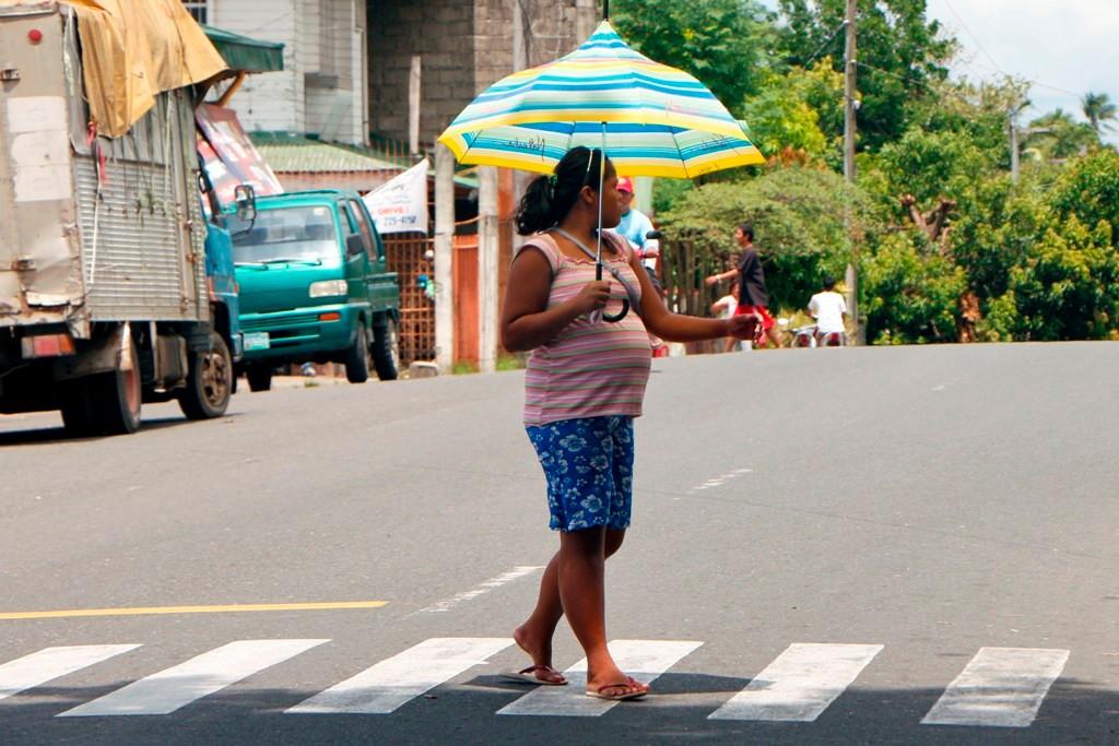 ...eine junge, stolze Filipina zu zweit mit Sonnenschirm in Dauin!
