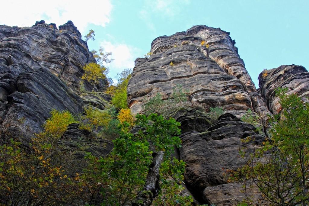Schroffe Sandsteinfelsen stehen unmittelbar neben dem Wanderweg