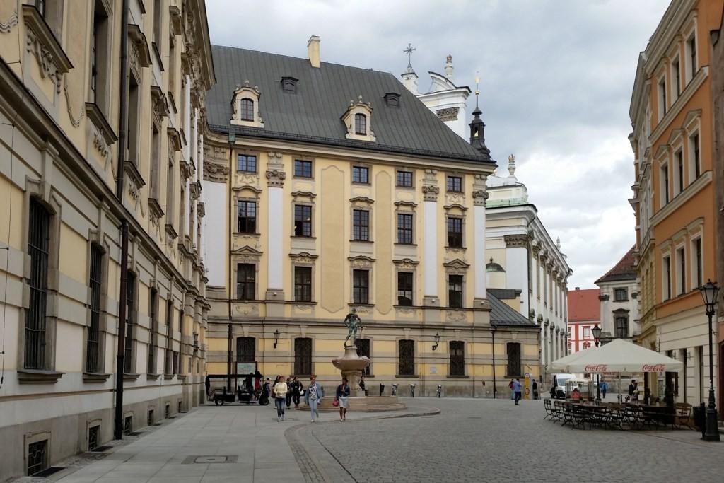 Universitätsgebäude mit Platz und der Skulptur des Fechters