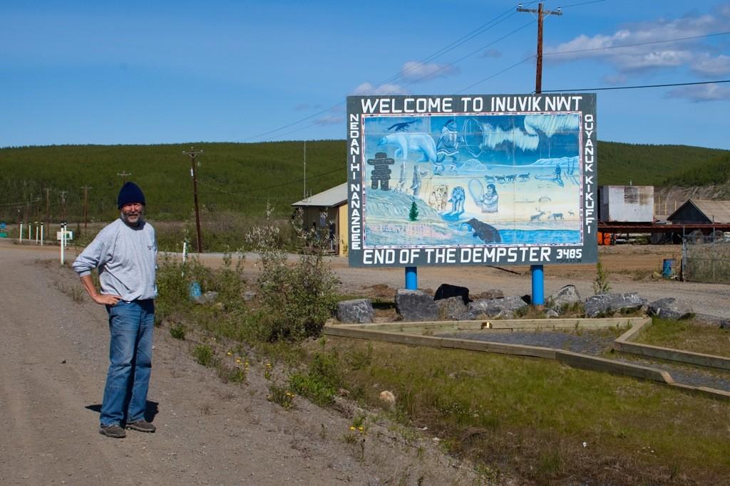 In Pose vor der Hinweistafel des Endes vom Dempster HWY in Inuvik, die zu diesem Zeitpunkt dort lebenden Einwohner, 3.485!