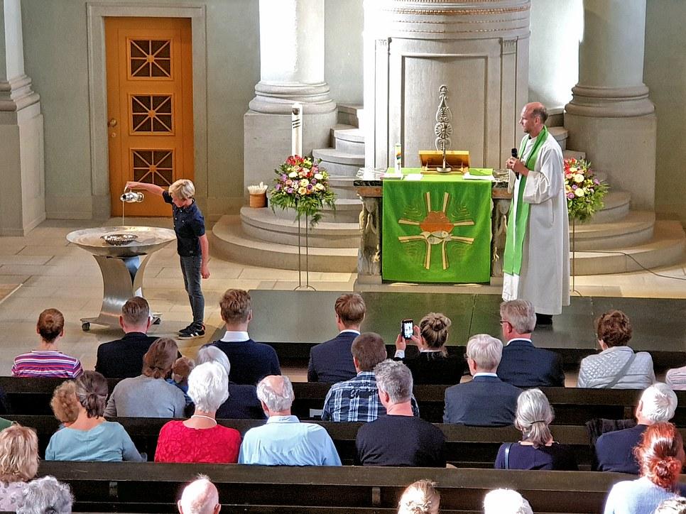 Das Weihwasser für die Taufe wird vorbereitet