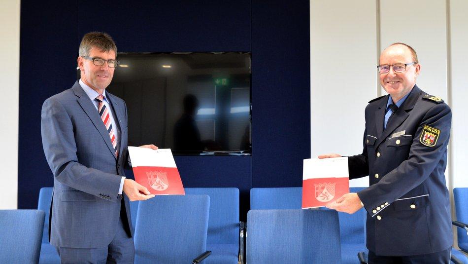 Prof. Dr. Michael Jäckel (Universität Trier) und Friedel Durben (Hochschule der Polizei HdP) mit den unterzeichneten Ausfertigungen des Kooperationsabkommens