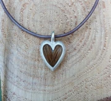 kleines Herz, 925/er Silbe Silber, mit eingelegtem Haar, mit Gießharz verschlossen,   LxB = ca. 21x13mm, €100,-