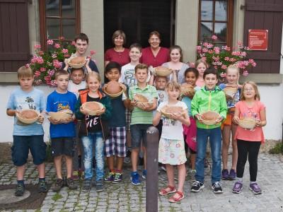 Kinder des Sommerferienprogramms präsentieren selbstgebackenes Brot