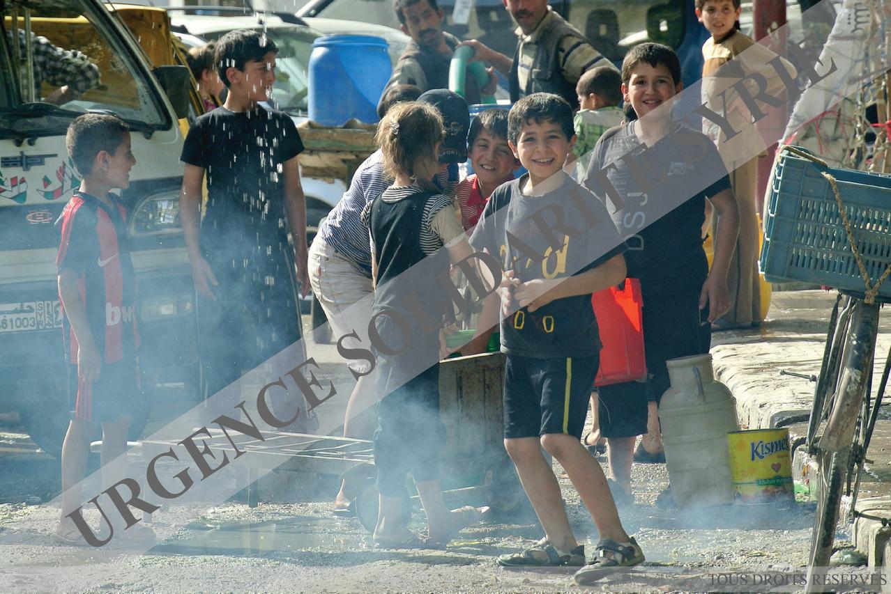 Des enfants jouent à un point de distribution d'eau, dans le quartier Al Myassar, à Alep le 08/05/2013.