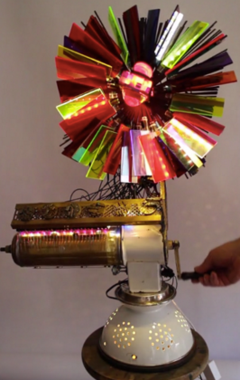 Assemblage light art sculpture made from a spaghetti strainer, a meat grinder, a chimney sweep brush, a water bottle, and watch parts. When the meat grinder is turned, LEDs behind the plexiglas are lit up, cause by the making of an electrical connection.