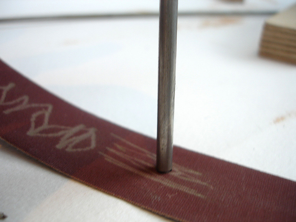 Slide cut rod backwards and forwards on carbide or emery paper until cut marks smoothed away.