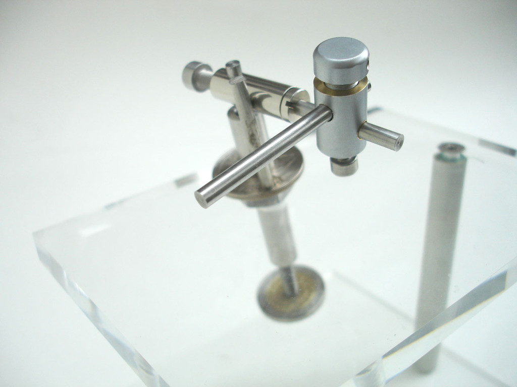 Side view showing needle shaft and illustrating large shaft retaining screw head allowing for easy back and forward positioning of needle tip. Bottom screw adjusts horizontal angle of needle
