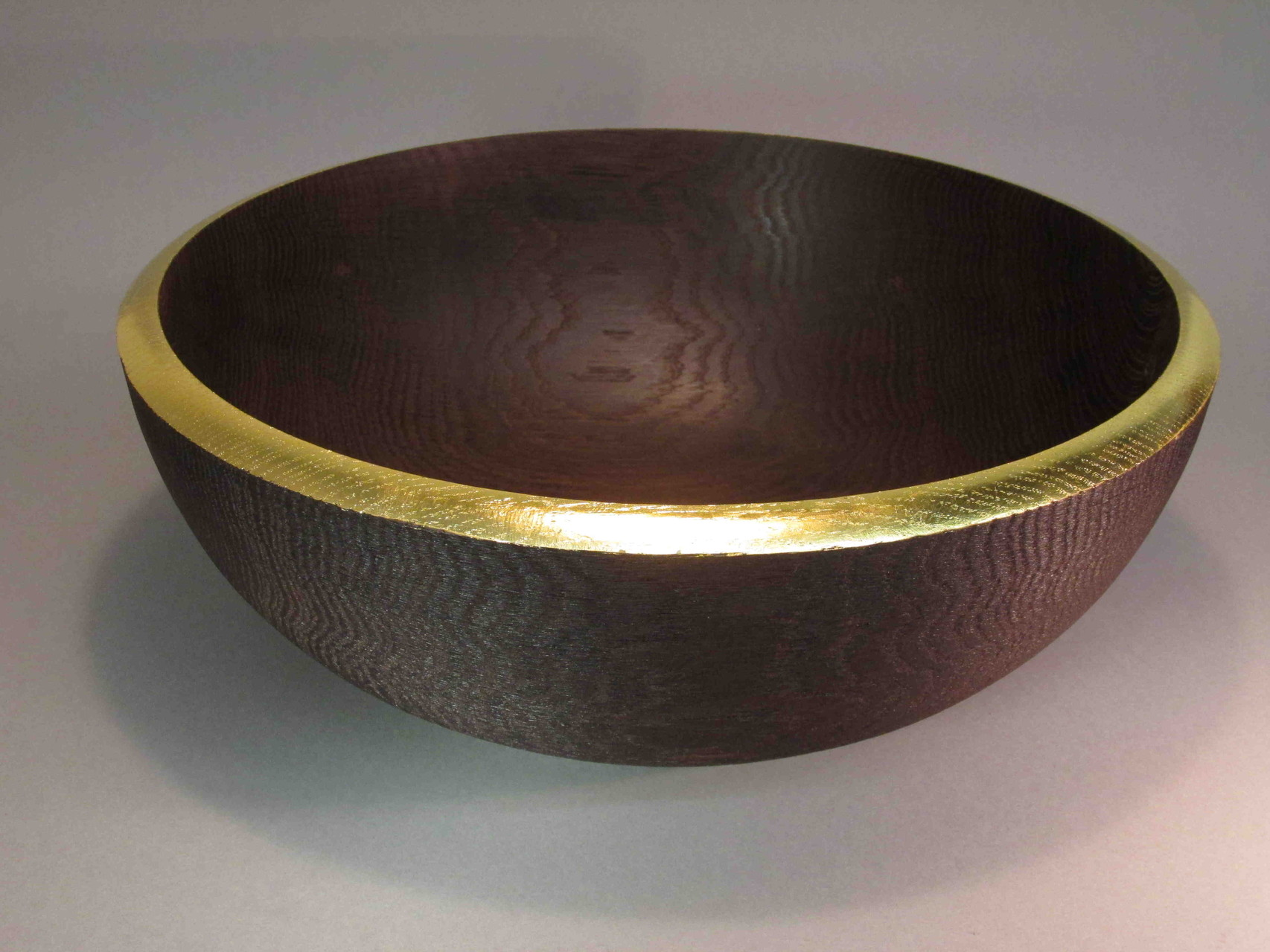 Dekoschüssel aus geräucherter und außen gebürsteter Eiche. Rand mit 24 krt Blattgold belegt