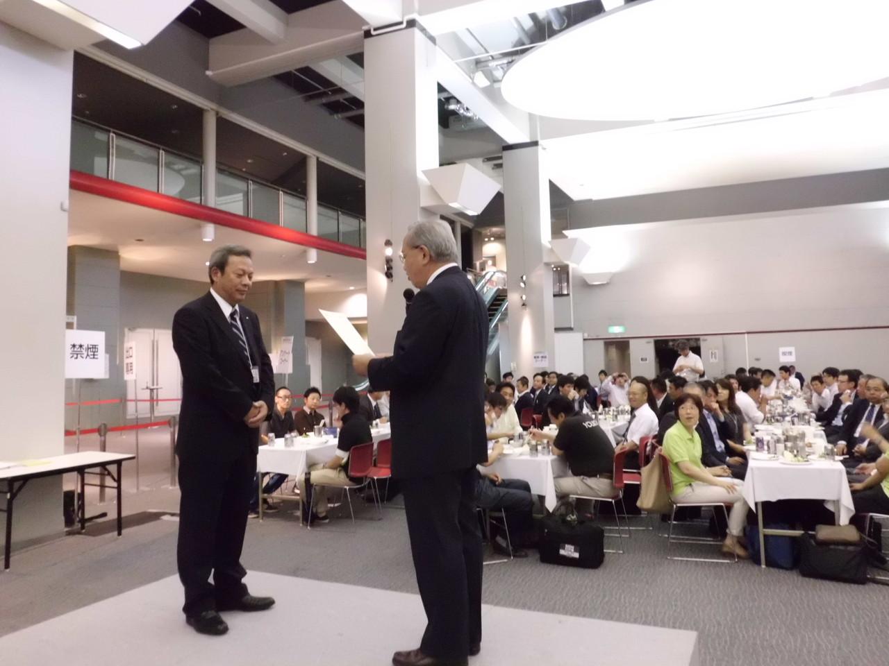 実行委員会により最優秀ブースデザイン賞は、(株)キヌガワ様に決定。会長より賞状と記念品の授与。