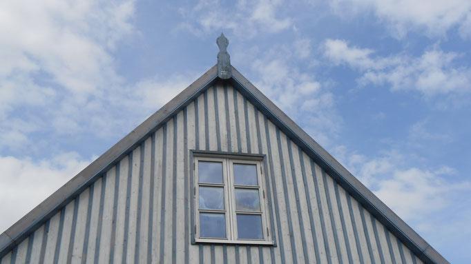 Der blau-weiß gestreifte Giebel des Ferienhauses vor blauem Himmel.