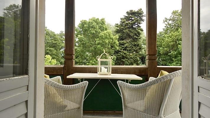 Blick in den Schlosspark durch die geöffneten Balkontüren der Ferienwohnung.