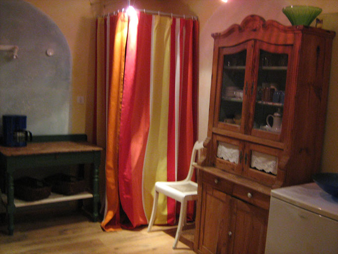 Eine Seite der Küche mit angrenzendem Bad