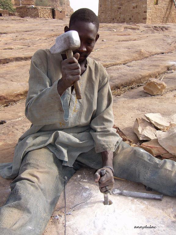 Dans les travaux de terrassement , Atemelo  veut agrandir la surface habitable de son village, il creuse dans le grès qui constitue la falaise.