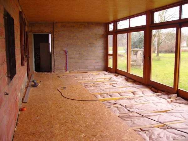 Der Verandaboden wird ausnivelliert, isoliert und mit OSB-Platten abgedeckt