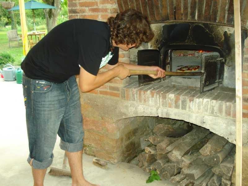 Noah schiebt die Pizzas in den Ofen
