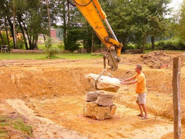 """Auch die Steine für die Basis des""""Quellsteins"""" werden mit dem Baqgger platziert"""