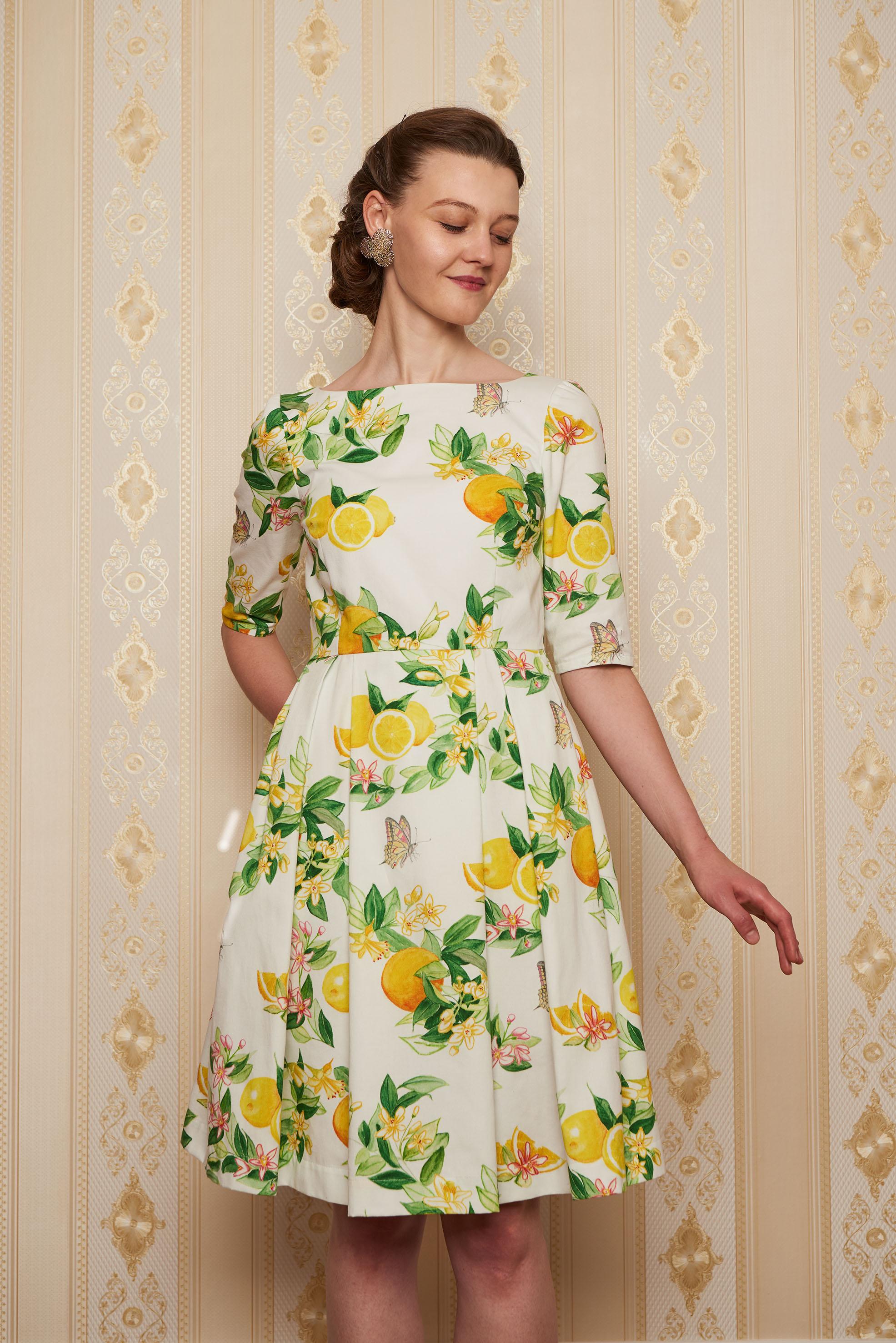 Klassisches knielanges Kleid mit halblangen Ärmeln, mit Zitronen, Orangen und Schmetterlingen bedruckte Baumwolle und zwei Nahttaschen. Fröhlich, elegant und beschwingt.