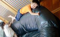 革張りソファの上で遊ぶ子供たちの写真