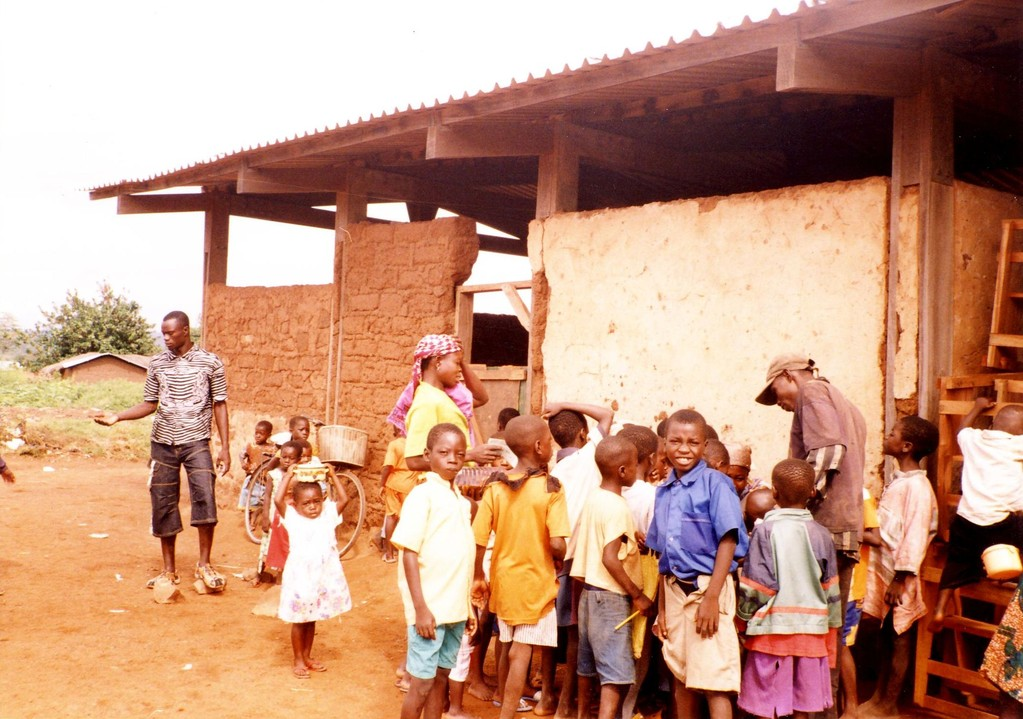 Mr. Seidu (far left) with children and villagers in front of the school building